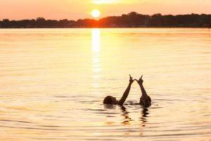 Students in lake making a W with their hands