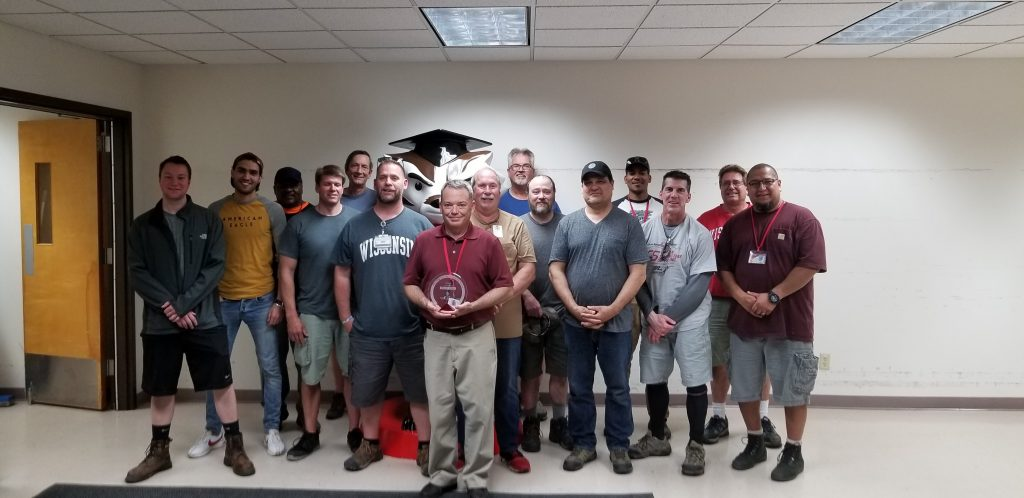 Photo of Brad Schenkel and 14 colleagues from the Campus Services team within the Physical Plant department