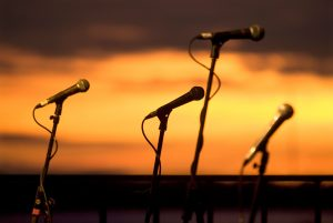 Four microphones against a sunset backdrop