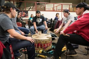 UW-Madison students sing a welcome song and play a drum during a Native November feast event
