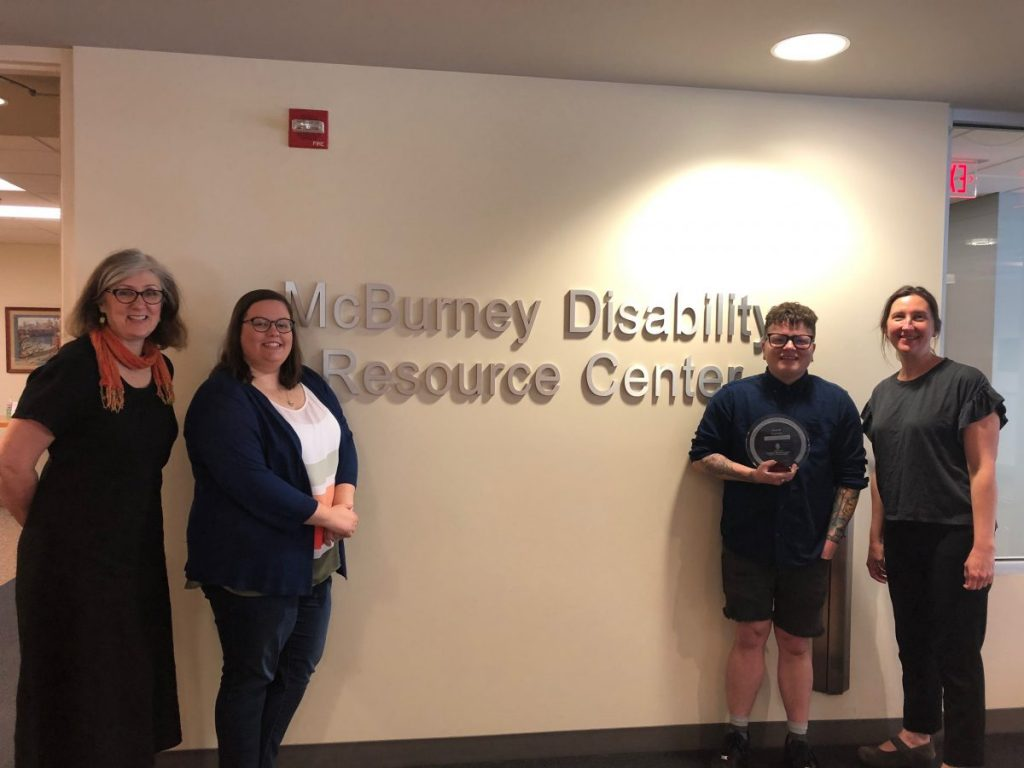 Photo of Peggy Weaver, Kate Doran, Caelyn Randall, and Amy Free standing in front of the McBurney Disability Resource Center wall sign