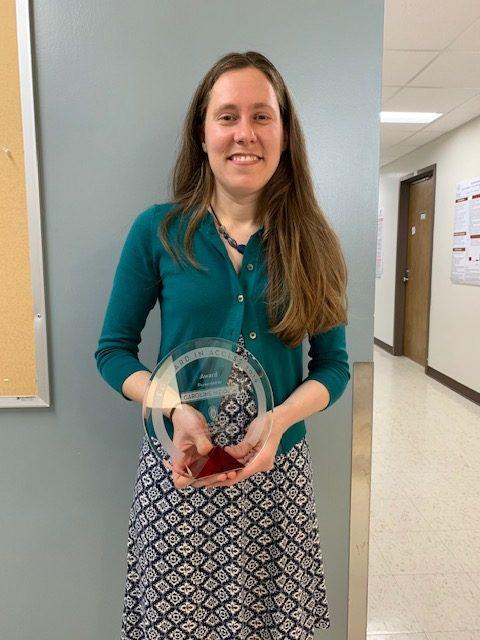 Carrie Niziolek holding award