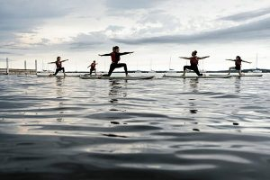 Students participating in a SUP class on the lake