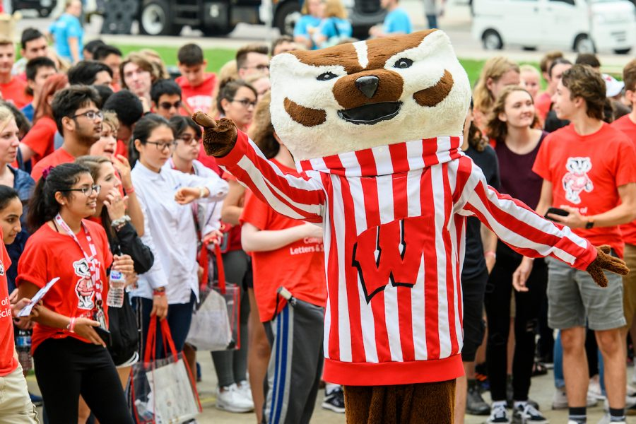 Bucky Badger in front of a crowd of students