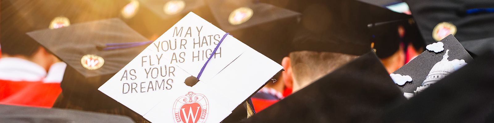 "UW–Madison decorated graduation caps with one that reads, ""May your hats fly as high as your dreams"""
