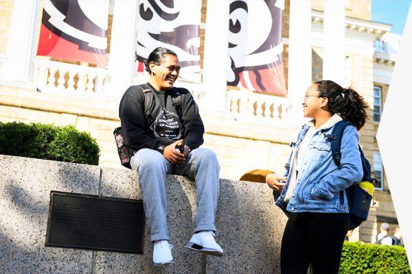 Undergraduate students taking a break, talk in front of Bascom Hall.