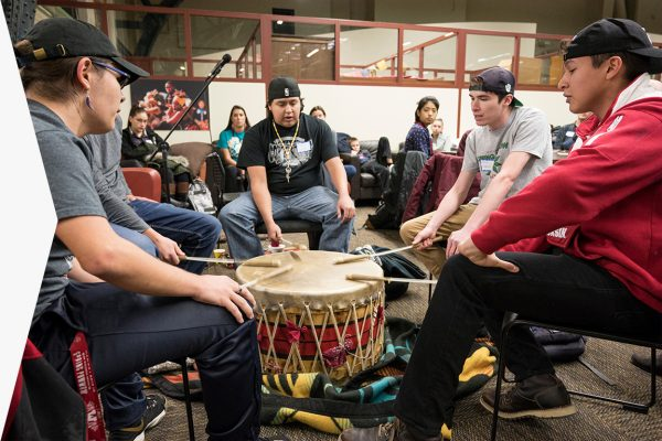 UW Madison students sing a welcome song while sitting around a drum at Native November feast