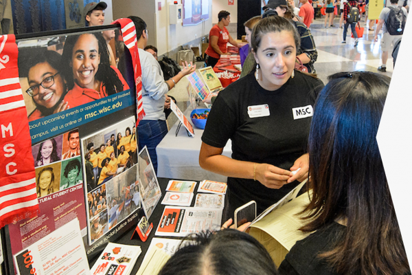 At the Student Org Fair, a student talks to a woman from the Multicultural Student Center