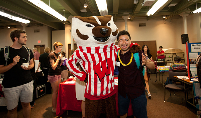 Student has an excited look on his face while posing for a photo with Bucky.