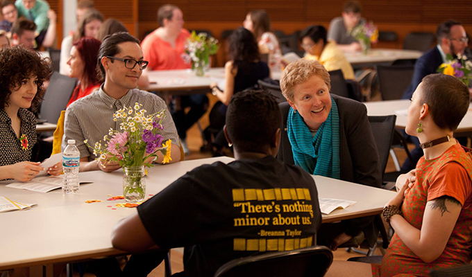 Mentors and students meet and talk with each other while sitting at a table during an event.