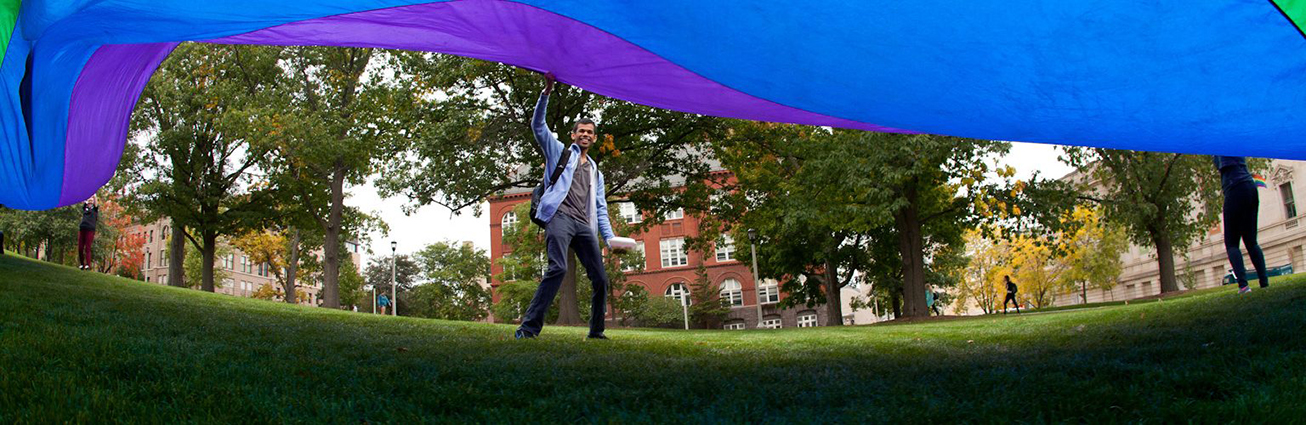 Student waves large rainbow flag while standing on the grass at Bascom Hill.
