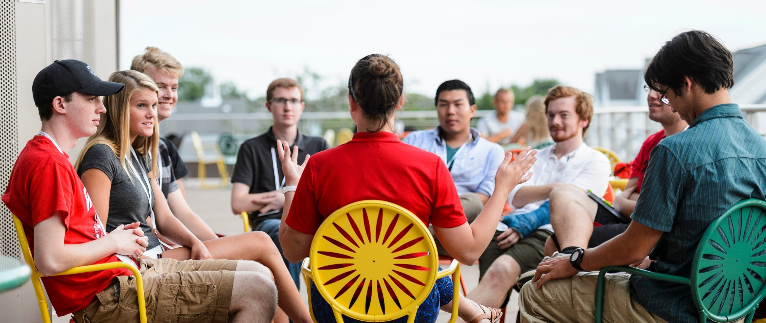 A small group of students sit in a circle while a leader guides them through their SOAR session outside of the Union South Plaza.