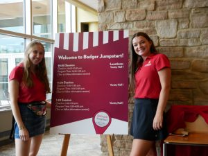 Student staff from the Center for the First-Year Experience welcome #FutureBadgers and their guests in front of a sign.